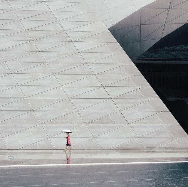 A person with an umbrella walking in front of the Museum of Contemporary Art in Shenzhen, China