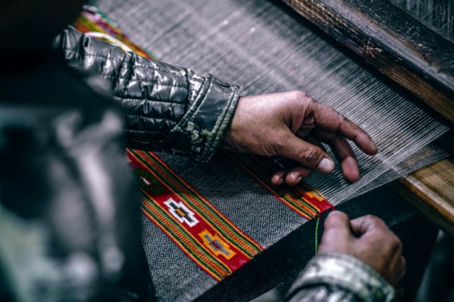 A person creating textiles at a loom.
