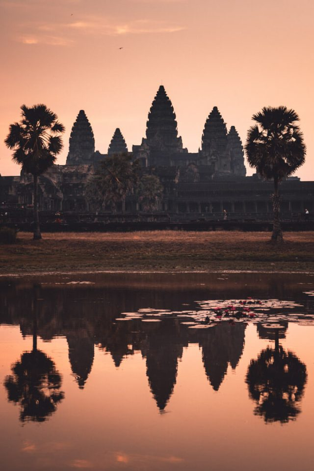 The sunset over a Cambodian temple reflecting in nearby water