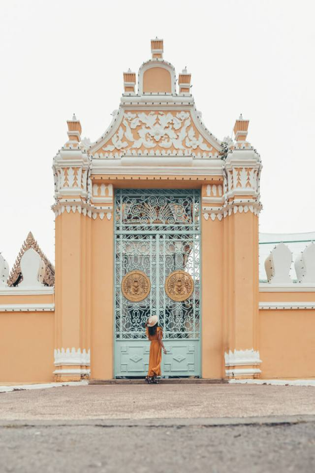 A woman in a yellow dress standing before a regal gate of blue and gold in Cambodia