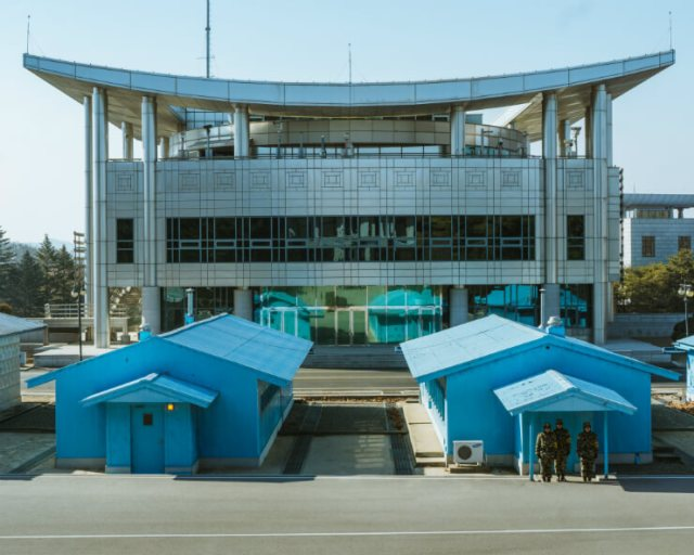 Three guards on duty before Panmon Hall in the DMZ Zone of North Korea