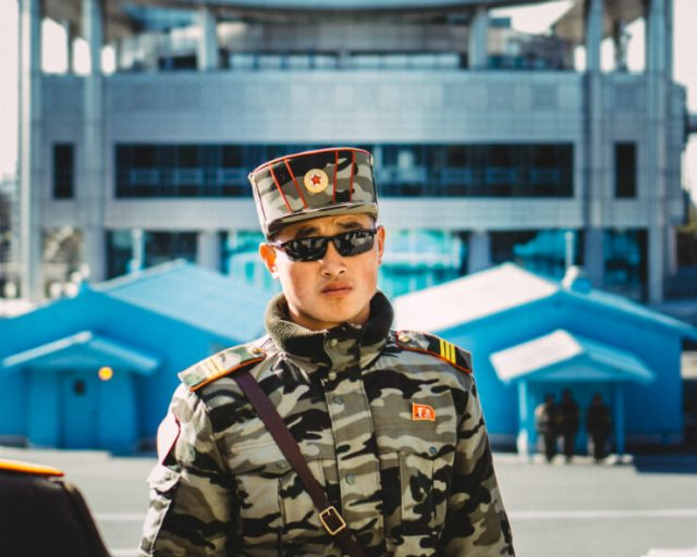 A DMZ guard standing before Panmon Hall in the DMZ Zone in North Korea