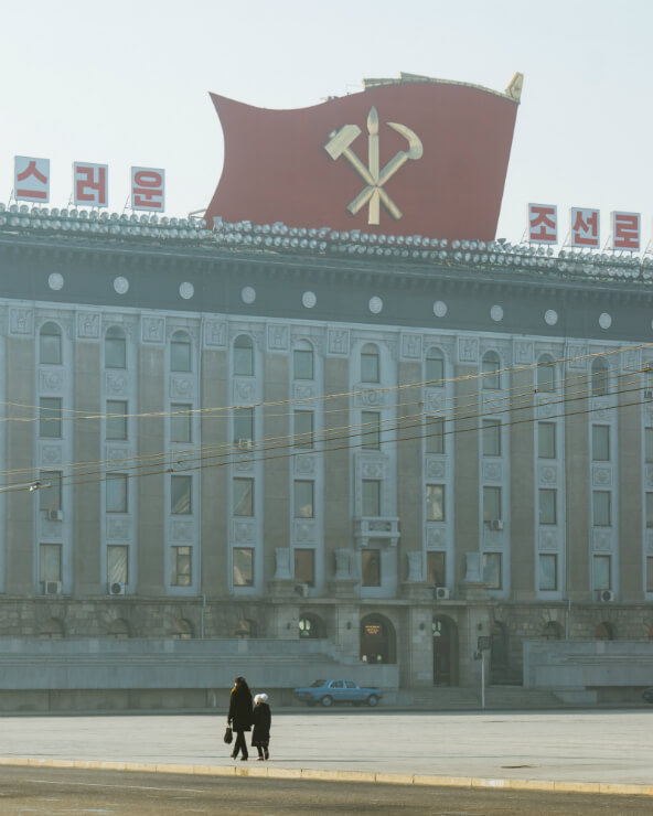 Two people walk before goveernment buildings in North Korea