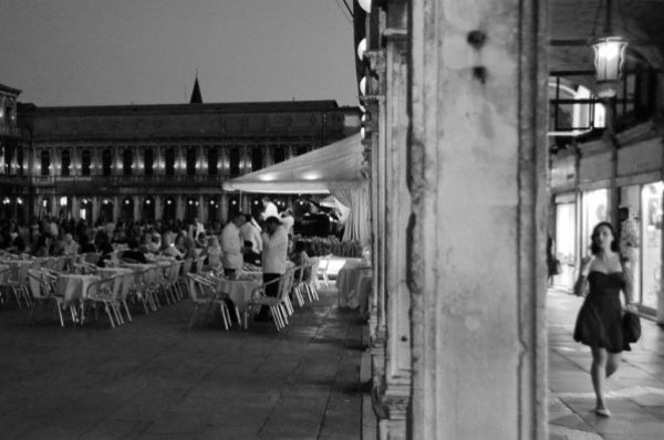 A woman walks by a Venice piazza at night