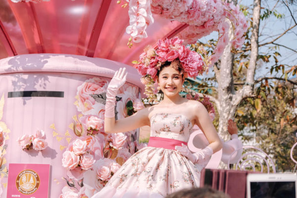 A beauty queen dressed all in pink waves to the camera in Chiang Mai in a photo by creative Denis Amirtharaj.