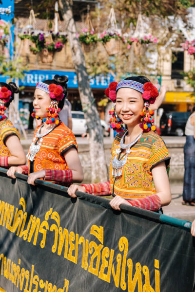 Performers in traditional garb carry a banner in a Chiang Mai parade.