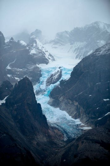 A large blue glacier between mountains.