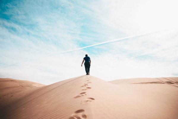 Man walks over sand dunes leaving footprints behind him