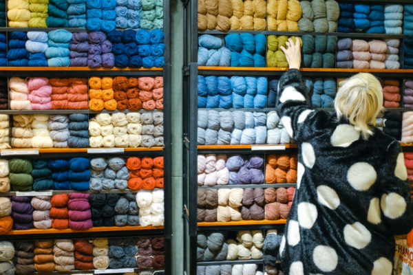 Person reaches up to select a ball of wool from a colourful wall display