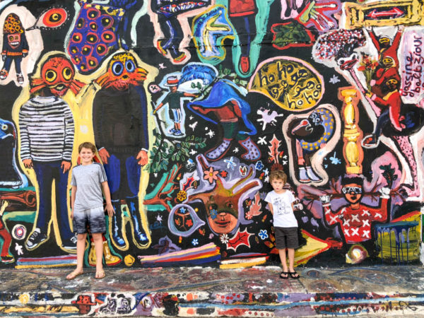 Two boys pose in front of a mural in Fez