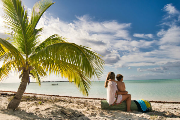 A mother and sun sit on a tropical beach under the shade of a palm tree