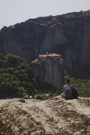 A man sitting in the foreground over looking a monastery in Meteora, Greece.