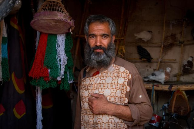 A merchant stands in the door of his shop in central asia.