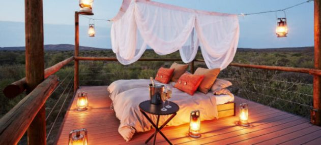 A luxurious mosquito-draped bed atop a raised wooden platform overlooking the grasslands