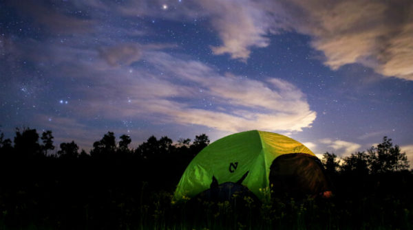 A green tent beneath the night sky in Hocking Hills, Ohio