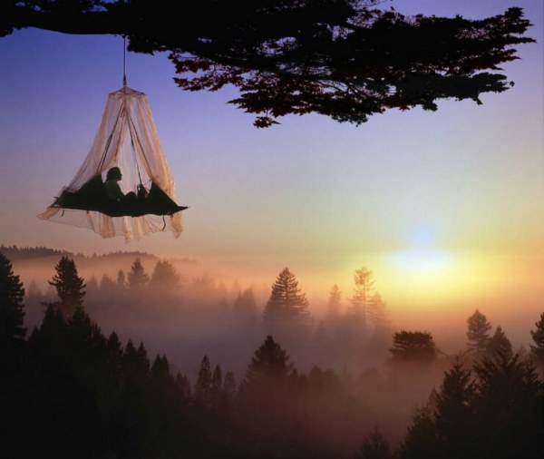 Hanging portaledge tent over dark misty forest at sunset