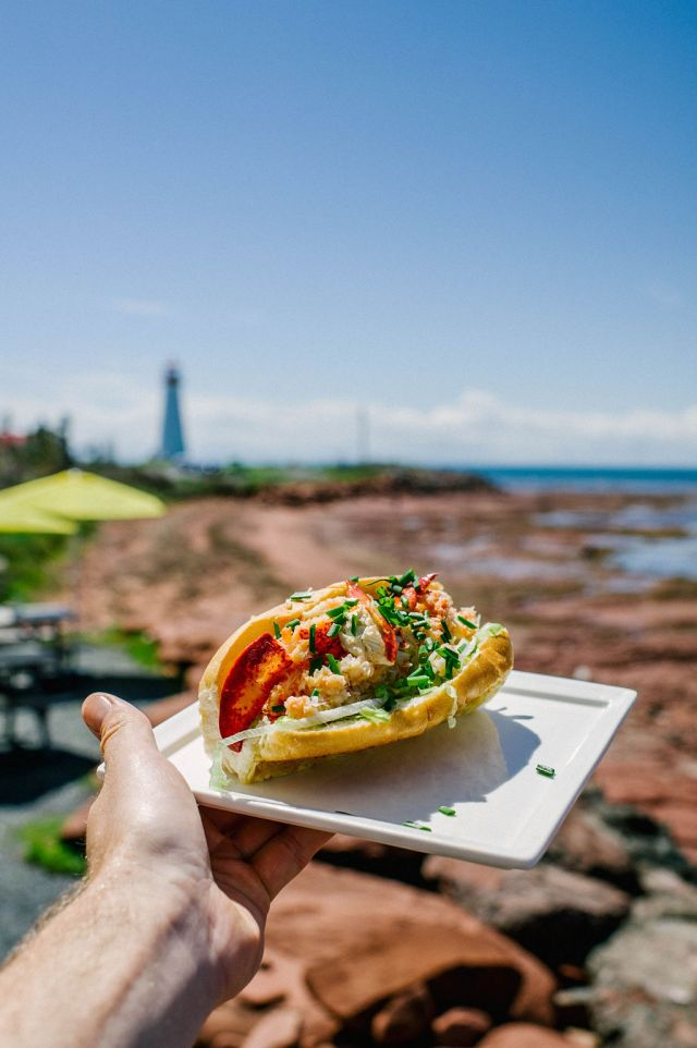 A man holding a plate of seafood with point prim lighthouse on prince edward island in the distance.