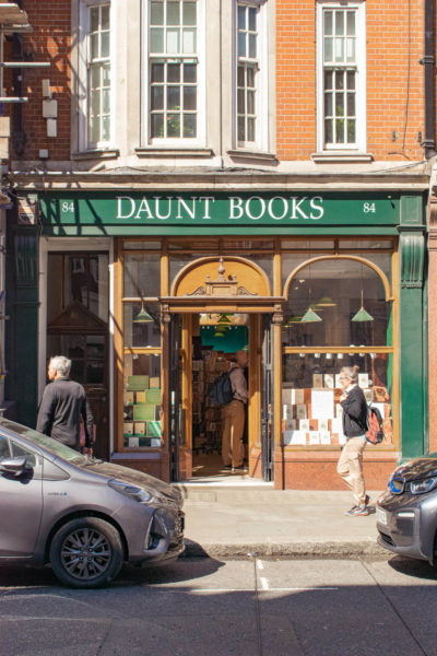 a tourist walks past a bookstore in london.