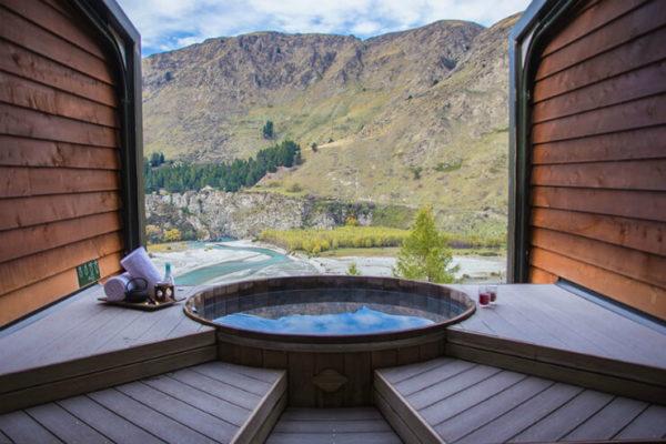 View of cedar-lined hot tub overlooking alpine valley in Queenstown