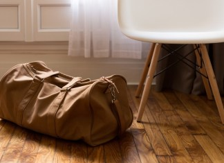 a brown suitcase rests on the floor next to a chair