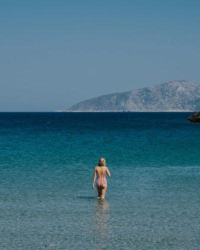 A woman walking in turquoise water in Greece