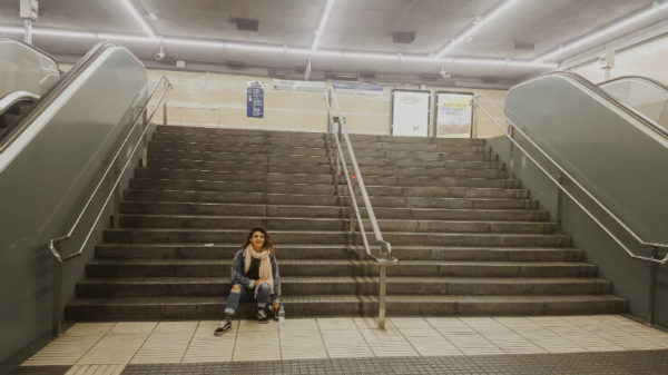 Dilara sits on the steps of an underground train station