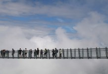 people stand on whistler bridge in canada amongst the clouds