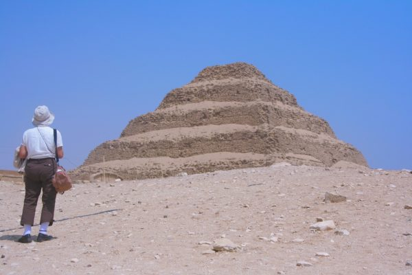 a woman stands before the temple of djoser