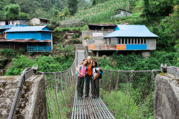 trekking family on rope bridge