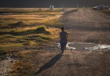 a boy running down a rural road