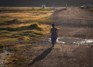 a boy running down a rural road
