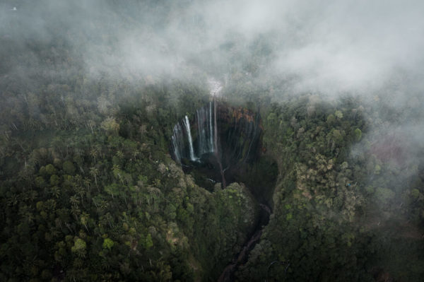 waterfall surrounded by clouded forest
