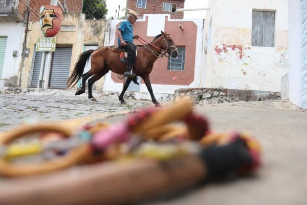 man astride horse in rural town