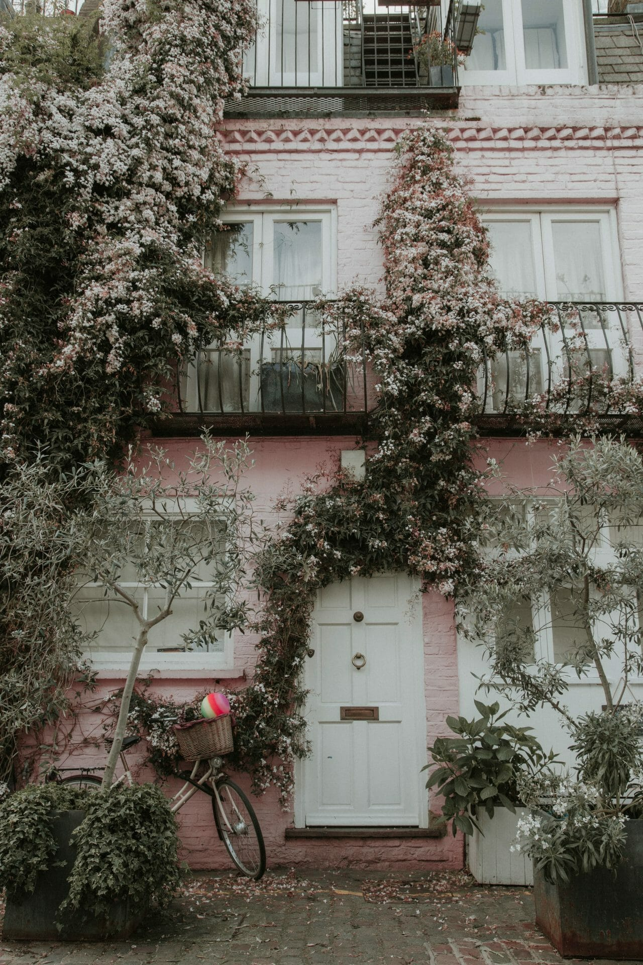 Picture of a pink home with flowers growing up the front for Real Estate News for Investors Podcast Episode #692