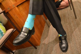 Senate Majority Leader Michael Sanchez wearing socks with pizza and cokes on them, a reference to the incident with Martinez at the Eldorado Hotel in December. Photo Credit: Andy Lyman.