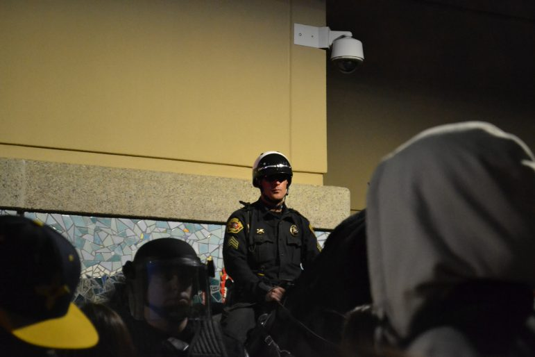 A mounted police officer and a police officer in riot gear stand between protesters and the Albuquerque Convention Center.