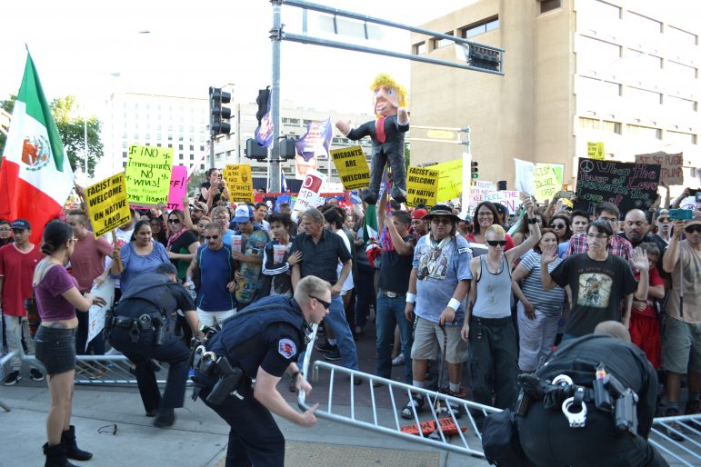 Protesters, mainly those who don't want to run through, stand while police lift up barriers.