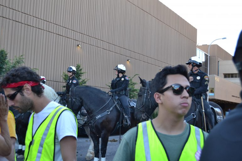Mounted police look on as peacekeepers stand hand-in-hand between them and other anti-Trump protesters.