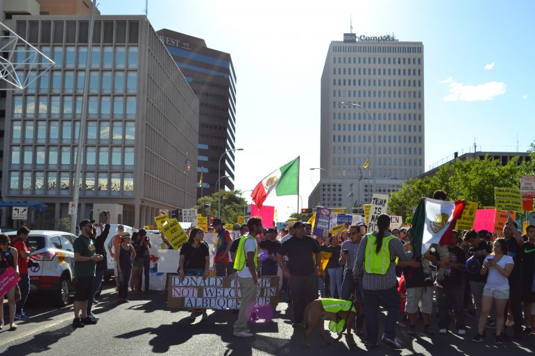 Protesters pause while marching in downtown Albuquerque near Civic Plaza.