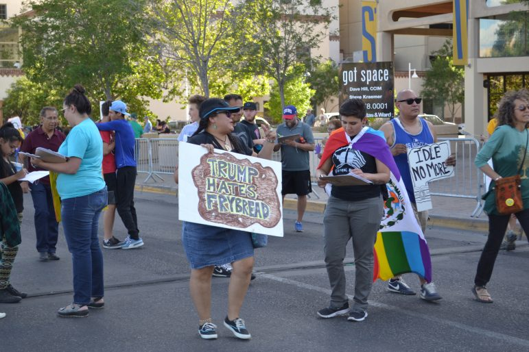 """""""Trump hates frybread"""" one protester's sign says."""
