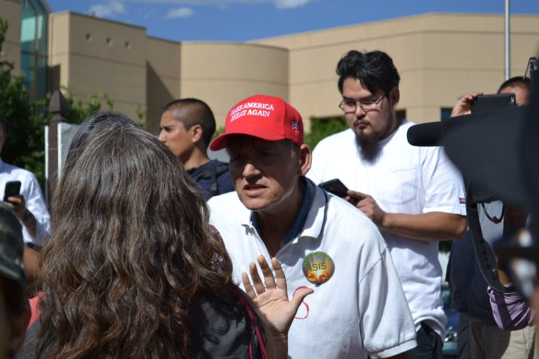 """A Donald Trump supporter with a """"Make America Great Again"""" hat argues with an anti-Trump protester."""