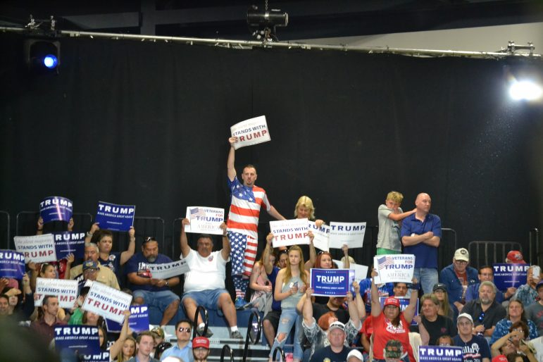 Donald Trump supporters wait for Trump to begin speaking.