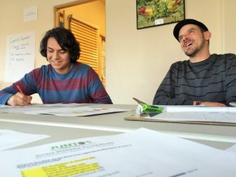 Robin Carreón (L) and Juntos Community Organizer, Michael Pitula, talk about the environmental group's work on climate change and air quality.
