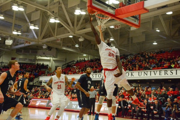 Senior forward Jameel Warney (No. 20, above) lays the ball in against New Hampshire. Warney is the two-time defending America East Player of the Year. HEATHER KHALIFA/THE STATESMAN