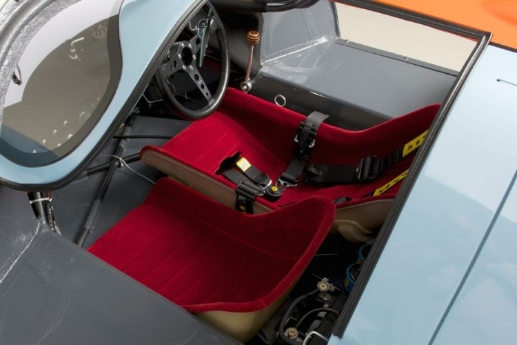 The driver and passenger seats are both upholstered in a deep bright red velour