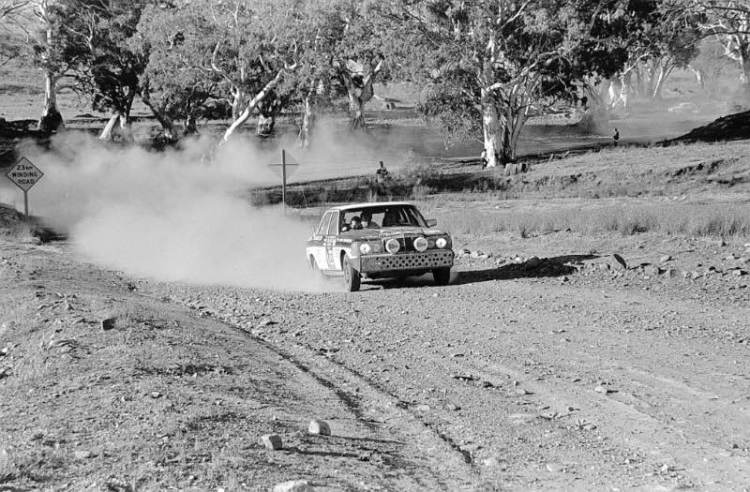 The winner-to-be of the 1977 London–Sydney Rally on a gravel track in Australia. Andrew Cowan and his co-drivers Colin Makin and Mike Broad win the rally in their Mercedes-Benz 280 E (W123).