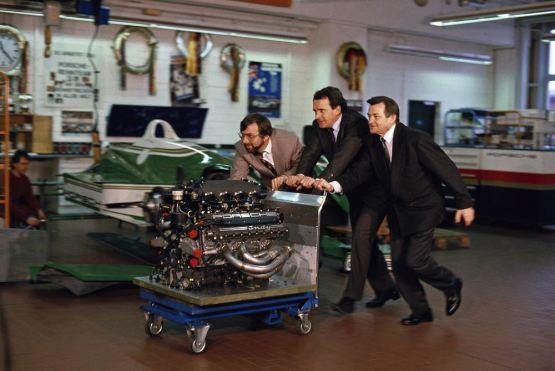 Hans-Joachim Esch, Helmut Flegl and Hans Mezger (l-r) with the engine Type 2708, 1990.