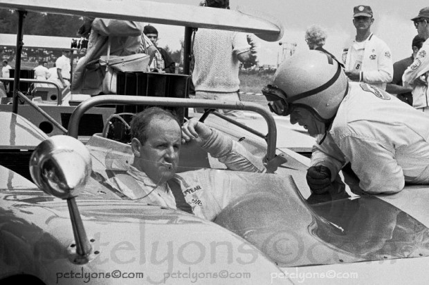 Dennis Hulme sitting in McLaren M8B listening to Bruce McLaren