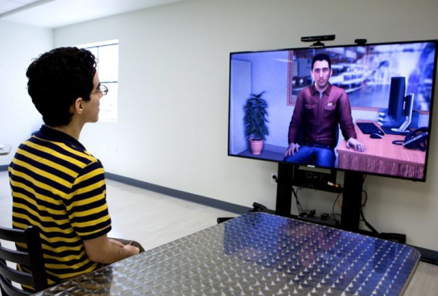 Young man practicing interviewing skills with an avatar on a big screen.