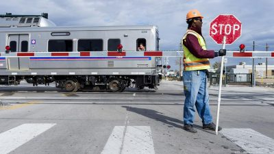 Workarounds: A construction worker holding a stop side due to gate timing issues on the Denver RTD line to the airport